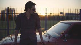 Retrato do homem considerável com seu carro poderoso clássico velho na rua, no por do sol ou no nascer do sol filme