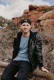 Retrato do homem considerável de viagem ocasional bonito novo que sorri perto das rochas vermelhas do deserto antigo na parte ext fotos de stock