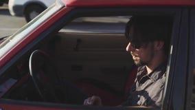 Retrato do homem considerável no carro poderoso clássico velho na rua, no por do sol ou no nascer do sol filme