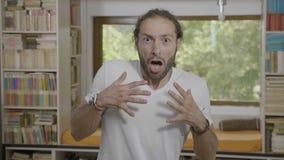 Retrato do homem considerável novo em casa que olha surpreendido mãos gritando e de levantamento chocadas e assustado - filme