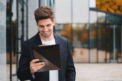 Retrato do homem considerável novo no revestimento com documentos, contas de serviço público, relatório Homem de negócios perto d fotografia de stock royalty free