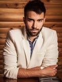 Retrato do homem considerável novo no terno branco contra o fundo de madeira Foto de Stock