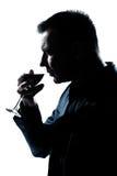 Retrato do homem da silhueta que cheira o vidro de vinho vermelho imagem de stock