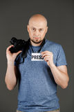 Retrato do homem de meia idade considerável na camisa cinzenta com o crachá do photocamera e da imprensa que levanta sobre o fund imagens de stock royalty free