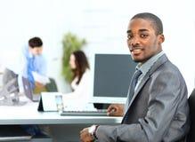 Retrato do homem de negócio afro-americano de sorriso com executivos