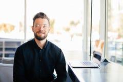Retrato do homem de negócio farpado novo na frente de seu lugar de funcionamento no escritório moderno foto de stock royalty free