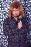 Retrato do homem de negócio sério na camisa preta com testes padrões em um chapéu forrado a pele Fotografia de Stock Royalty Free