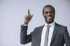 retrato do homem de negócios afro-americano feliz que aponta acima e que olha a câmera fotografia de stock royalty free