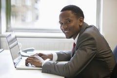 Retrato do homem de negócios afro-americano feliz que usa o portátil na mesa de escritório imagem de stock royalty free