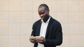 Retrato do homem de negócios afro-americano no terno que conta a posição do dinheiro perto do centro do escritório Ele que comemo vídeos de arquivo