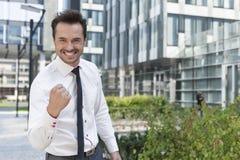 Retrato do homem de negócios alegre com prédio de escritórios exterior ereto apertado do punho imagem de stock