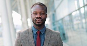 Retrato do homem de negócios americano do africano negro novo que está perto das janelas grandes do prédio de escritórios e que o video estoque