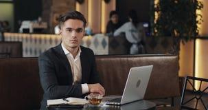 Retrato do homem de negócios bem sucedido novo que senta-se no café com portátil e que olha na câmera vídeos de arquivo