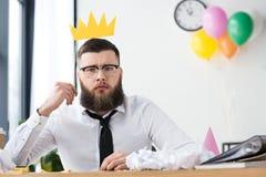 retrato do homem de negócios com a coroa de papel no local de trabalho imagem de stock royalty free