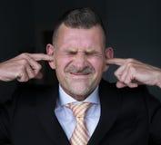 Retrato do homem de negócios com os dedos em suas orelhas fotografia de stock