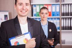Retrato do homem de negócios com um dobrador nas mãos e no seu colega Fotografia de Stock Royalty Free