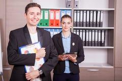 Retrato do homem de negócios com um dobrador nas mãos e no seu colega Imagens de Stock