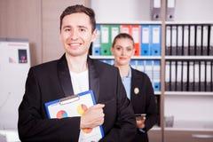 Retrato do homem de negócios com um dobrador nas mãos e no seu colega Fotos de Stock Royalty Free