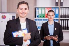 Retrato do homem de negócios com um dobrador nas mãos e no seu colega Fotografia de Stock