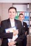 Retrato do homem de negócios com um dobrador nas mãos e no seu colega Imagem de Stock Royalty Free