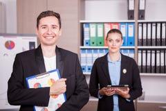 Retrato do homem de negócios com um dobrador nas mãos e no seu colega Foto de Stock Royalty Free