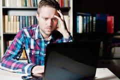 Retrato do homem de negócios concentrado nos vidros com portátil Imagem de Stock