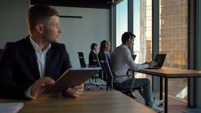 Retrato do homem de negócios considerável atrativo do chefe com a almofada digital no centro de atendimento filme