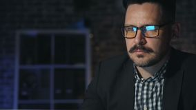 Retrato do homem de negócios considerável no funcionamento de vidros com o computador no escritório escuro filme