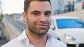 Retrato do homem de negócios considerável novo na camisa branca, sorrindo, feliz bem sucedido, no estacionamento perto do centro  vídeos de arquivo