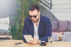 Retrato do homem de negócios considerável que guarda a tabuleta digital no café imagem de stock