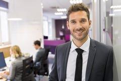 Retrato do homem de negócios de sorriso que levanta no escritório moderno, lookin Imagem de Stock Royalty Free