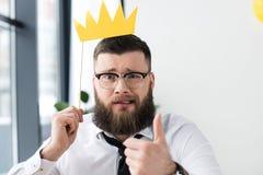 retrato do homem de negócios farpado com a coroa de papel que mostra o polegar acima fotografia de stock