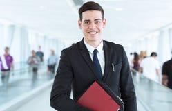 Retrato do homem de negócios feliz novo na frente do fundo moderno ocupado fotografia de stock
