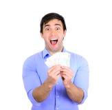 Retrato do homem de negócios feliz novo que guarda o dinheiro em suas mãos Foto de Stock