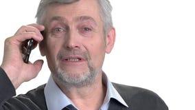 Retrato do homem de negócios maduro que fala no fundo branco filme