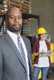 Retrato do homem de negócios masculino afro-americano seguro com o trabalhador fêmea que está no fundo fotografia de stock royalty free