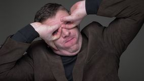 Retrato do homem de negócios de meia idade moreno alegre no terno que faz poses estranhas com prazer no fundo cinzento video estoque