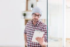Retrato do homem de negócios moderno com a porta do escritório da abertura do dispositivo da tabuleta imagem de stock royalty free