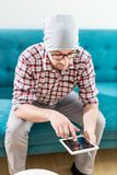 Retrato do homem de negócios moderno que senta-se no sofá e que olha a tabuleta digital imagens de stock
