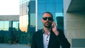 Retrato do homem de negócios nos óculos de sol que fala no telefone e que anda na rua Homem novo que tem a conversação do negócio video estoque