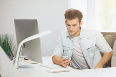 Retrato do homem de negócios novo considerável que senta-se na tabela do escritório com computador pessoal e que escreve no telef fotografia de stock royalty free