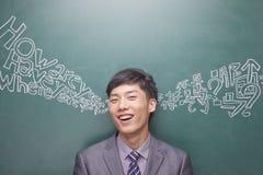 Retrato do homem de negócios novo de sorriso na frente da placa preta com o roteiro chinês e inglês que vem de cada orelha Fotos de Stock