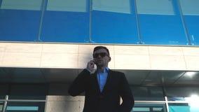 Retrato do homem de negócios novo nos óculos de sol que fala no telefone exterior perto do escritório Feche acima do homem de neg filme