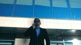 Retrato do homem de negócios novo nos óculos de sol que fala no telefone exterior perto do escritório Feche acima do homem de neg video estoque