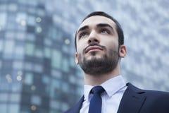 Retrato do homem de negócios novo sério que olha acima, fora, o distrito financeiro Imagem de Stock