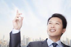 Retrato do homem de negócios novo seguro Gesturing, fora com arquitectura da cidade Imagens de Stock
