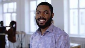 Retrato do homem de negócios preto profissional feliz do empresário com a barba e o sorriso bonito que levantam no escritório mod filme