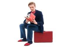 Retrato do homem de negócios que senta-se em sua mala de viagem quando e sorriso Imagem de Stock