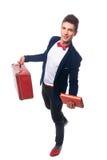 Retrato do homem de negócios que senta-se em sua mala de viagem quando e sorriso Fotos de Stock