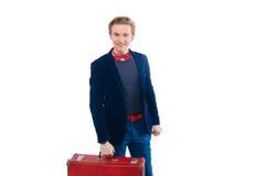 Retrato do homem de negócios que senta-se em sua mala de viagem quando e sorriso Fotografia de Stock Royalty Free